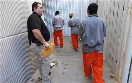This Jan. 13, 2016 photo shows Corporal Darryl Adkins, left, escorting inmates into the Greene County Jail from a Department of Corrections facility. (The Springfield News-Leader via AP)