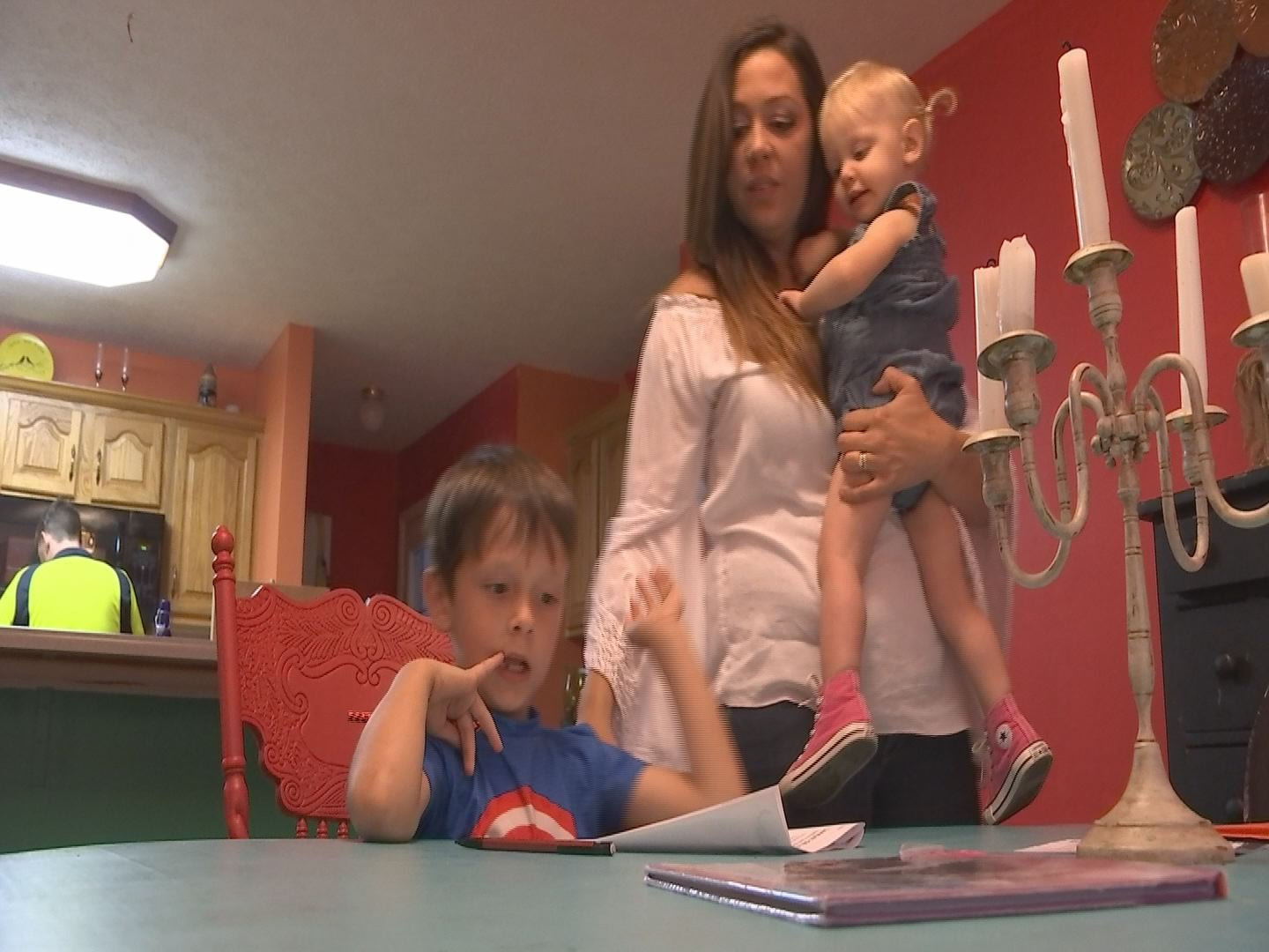 Mom Katie McClain helps her son Gunner with his homework in their Benton home, holding her daughter Sparrow. She hopes they learn to treat people well in person, and online.