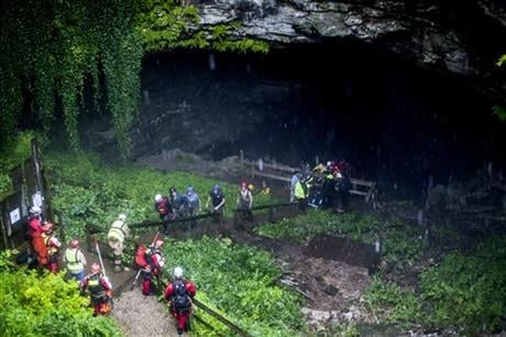 Rescued people walk out of the entrance to Hidden River Cave after officials said over a dozen people who exploring the cave were trapped by rising water Thursday, May 26, 2016, in Horse Cave, Ky. (Daily News via AP)
