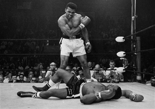 In this May 25, 1965, photo, Muhammad Ali stands over Sonny Liston shortly after dropping him with a short hard right to the jaw in Lewiston, Maine, in their world heavyweight bout. (AP Photo)