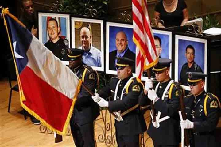 The Dallas Police color guard presents the colors before photos of five fallen officers being remembered during an interfaith memorial service at the Morton H. Meyerson Symphony Center in Dallas, Tuesday, July 12, 2016. (The Dallas Morning News via AP)