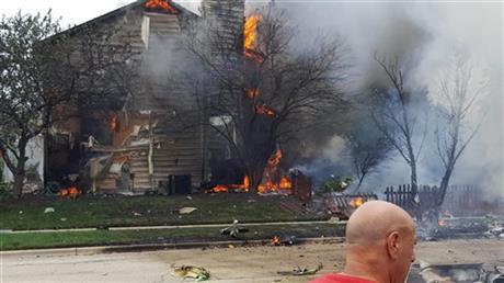 A home burns following a plane crash in Plainfield, Ill., Thursday, July 21, 2016. (Chicago Tribune via AP)