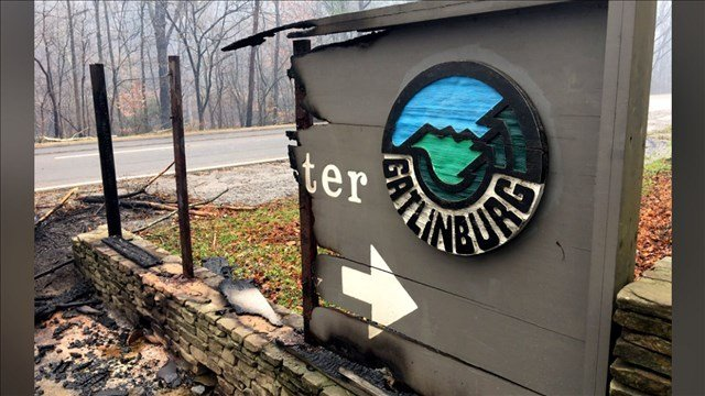 This Nov. 29, 2016, photo shows a Gatlinburg, Tennessee, visitors' center sign destroyed in wildfires that killed multiple people.