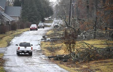 A vehicle drives down a street with fallen trees after a suspected tornado touched down in Tullahoma, Tenn., Wednesday Nov. 30, 2016. (The Tennessean via AP)