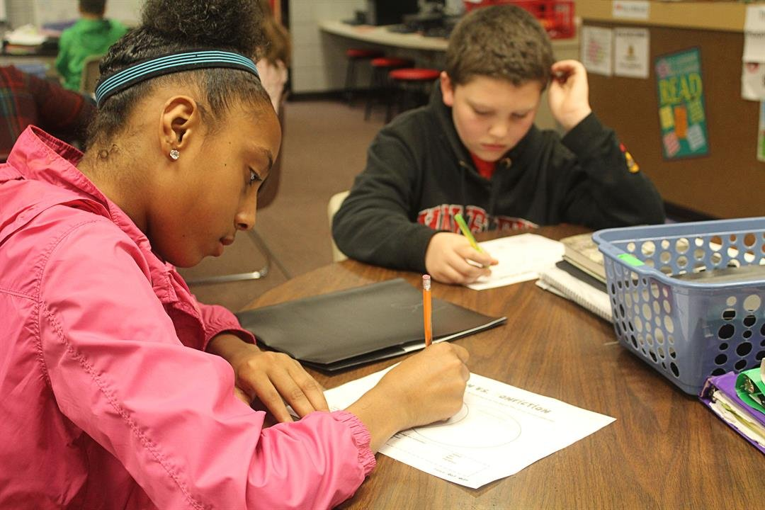 A'Sohntea Farmer and Joshua Saunders  concentrate on completing an assignment in the library at Mayfield Middle School.