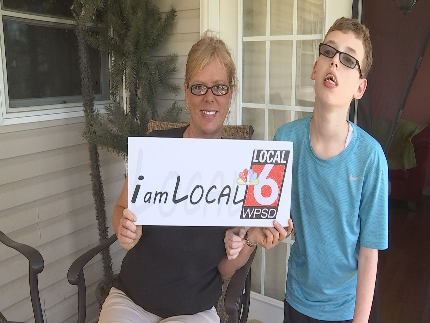 Matthew and his mom, Bethany, hold the I Am Local 6 sign during their story shoot.