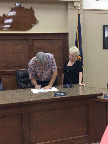 Marshall County Judge Executive Chyrill Miller signing an order to hold a wet/dry vote.