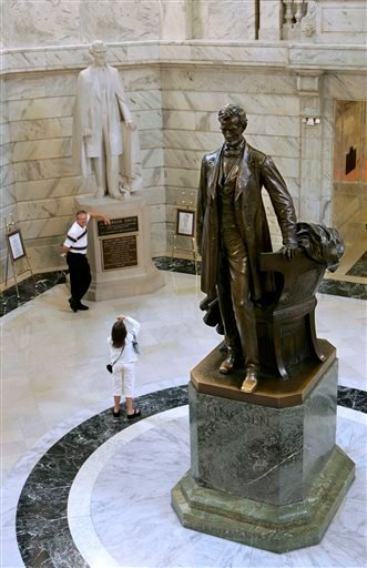 In this Aug. 5, 2008, file photo, tourists pose for pictures in front of the Jefferson Davis statue in the Capitol Rotunda as a statue of Abraham Lincoln towers in the foreground in Frankfort, Ky. (AP photo)