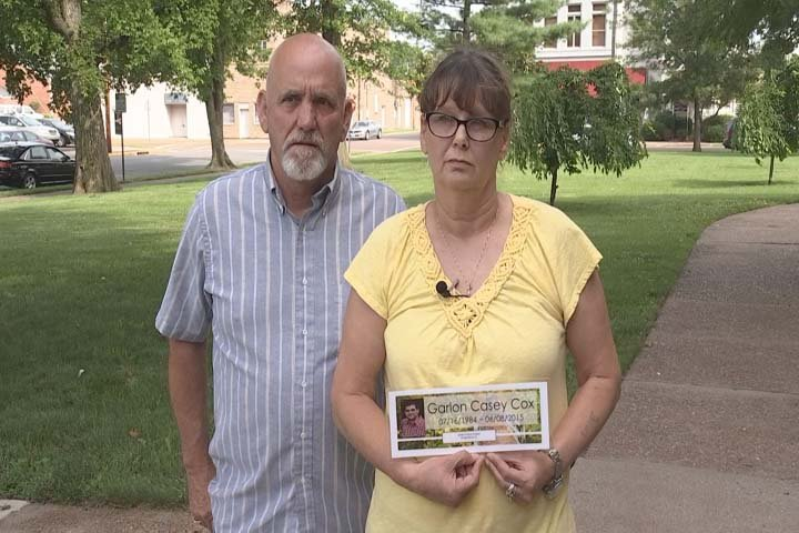 Ronnie and Barbara Cox hold a photo of their son outside the McCracken County Courthouse Thursday.