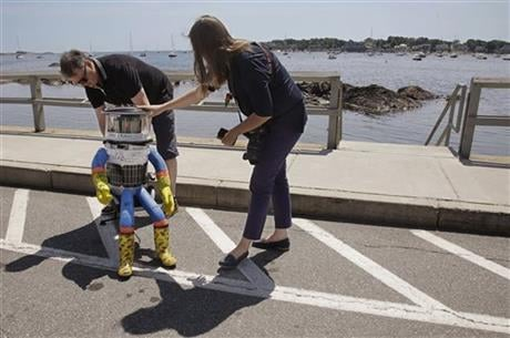 HitchBOT co-creator David Harris Smith adjusts its position as co-creator Frauke Zeller, right, says farewell as the hitchhiking robot starts its journey Friday, July 17, 2015, in Marblehead, Mass. (AP photo)