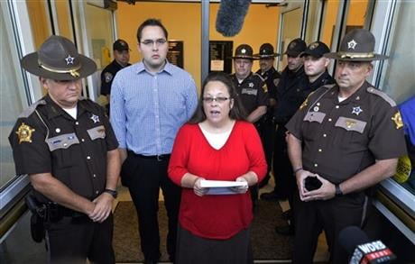 Surrounded by Rowan County Sheriff's deputies, Rowan County Clerk Kim Davis, with her son Nathan Davis standing by her side, makes a statement to the media at the front door of the Rowan County Judicial Center in Morehead, Ky. Sept. 14, 2015. (AP photo)