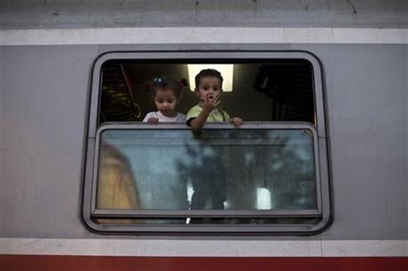 Children peer out of a window after they boarded a train close to Croatia's border with Serbia, in Tovarnik, Croatia, Monday, Sept. 21, 2015. (AP photo)