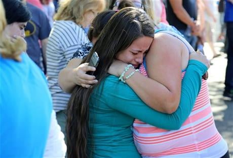 A woman is comforted as friends and family wait for students at the local fairgrounds after a shooting at Umpqua Community College in Roseburg, Ore., on Thursday, Oct. 1, 2015. (AP Photo)
