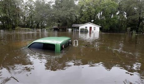 A vehicle and a home are swamped with floodwater from nearby Black Creek in Florence, S.C., Monday, Oct. 5, 2015 as flooding continues throughout the state following several days of rain. (AP Photo)