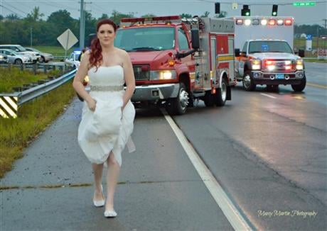 In this Oct. 3, 2015 photo provided by Marcy Martin Photography, her daughter Sarah Ray, in her wedding dress, attends to a car crash in Clarksville, Tenn. (Marcy Martin Photography via AP)