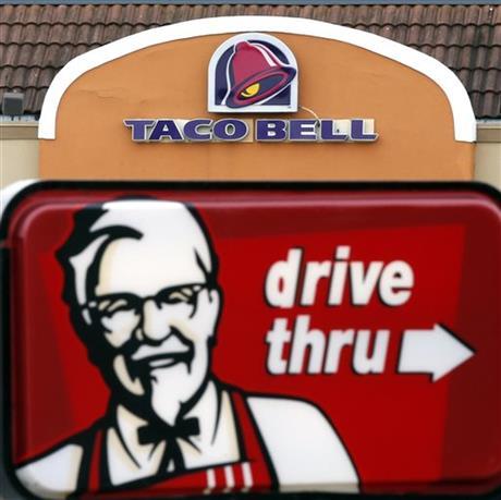 This Jan. 31, 2014, file photo, shows a Taco Bell facade behind a KFC drive-thru sign in Saugus, Mass. (AP photo)