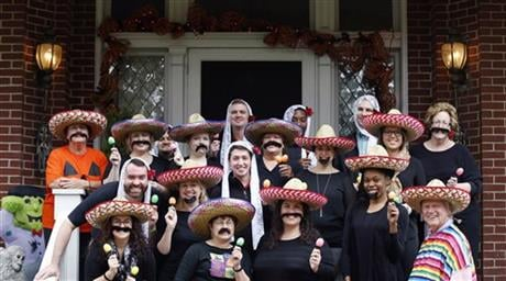 In this Oct. 28, 2015 photo, University of Louisville James Ramsey, lower right, and his wife, Jane, upper left, host a Halloween party in Louisville, Ky. (The Courier-Journal via AP)