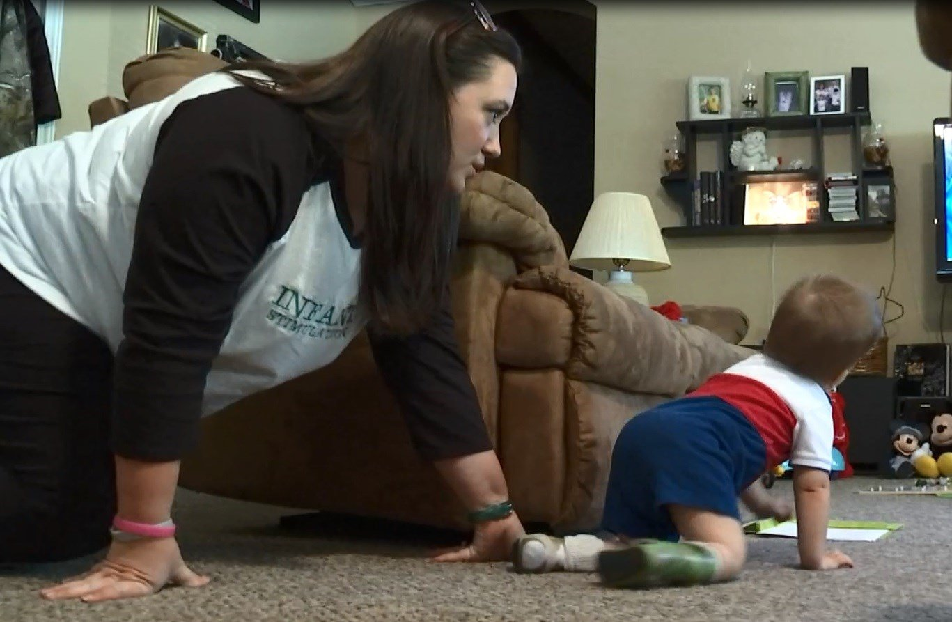 Early Interventionist Jessica Pryor crawls with Drake into the living room for exercises.
