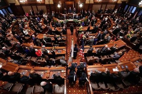 In this Jan. 14, 2015 photo, Illinois Gov. Bruce Rauner, center at podium, presides over swearing in ceremonies in the Senate chambers at the Illinois State Capitol in Springfield Ill. (AP photo)