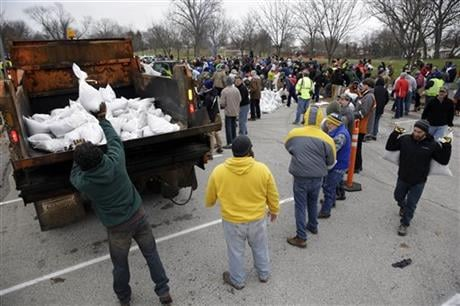 Volunteers form a human chain as they help load sandbags Tuesday, Dec. 29, 2015, in St. Louis. Flooding across Missouri has forced the closure of hundreds of roads and threatened homes. (AP Photo)