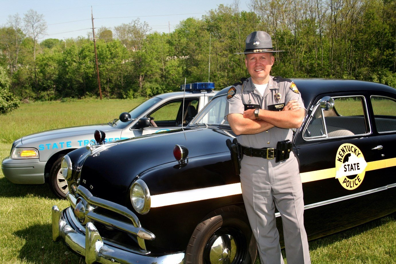 In this photo from Kentucky State Police, KSP Commissioner Rodney Brewer leans against a 1949 Patrol Cruiser.